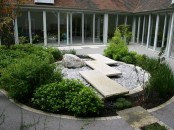 a Japanese-inspired backyard with much greenery, a rock garden and stone tiles over it