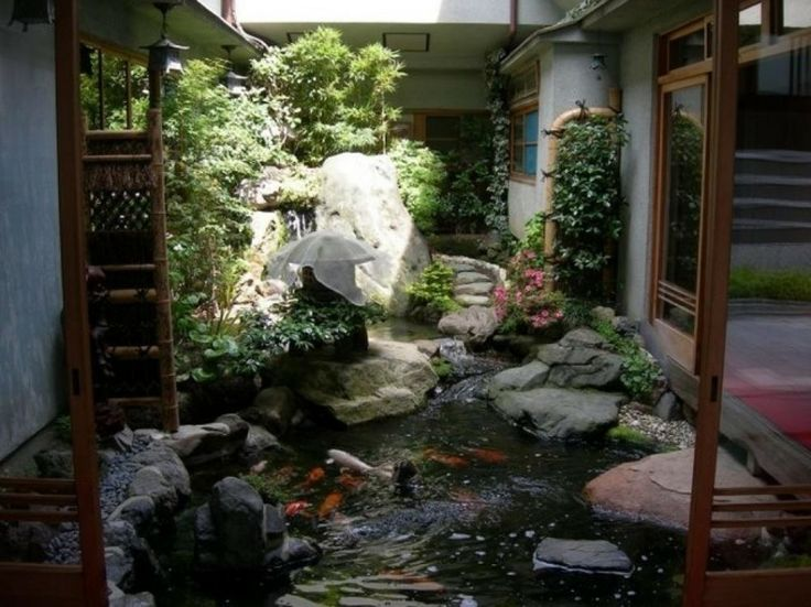 an amazing Japanese garden with a pond, a small waterfall, large rocks, greenery, a large Japanese lantern