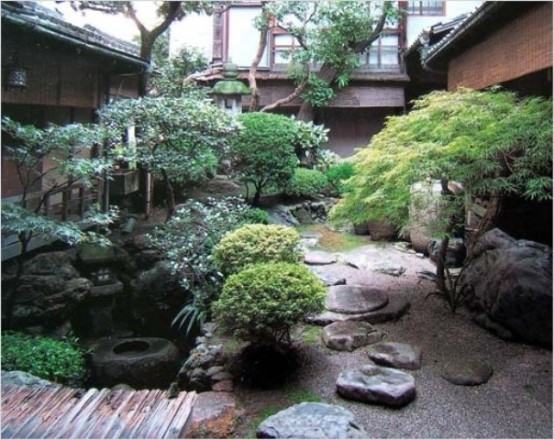 a calming Japanese garden with pebbles, large rocks, a wooden bridge, trees, lanterns and a pond