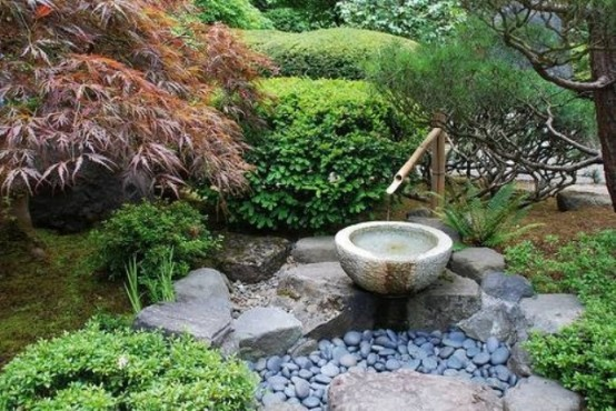 a small Japanese garden with pebbles, rocks, a bamboo fountain, greenery and trees around