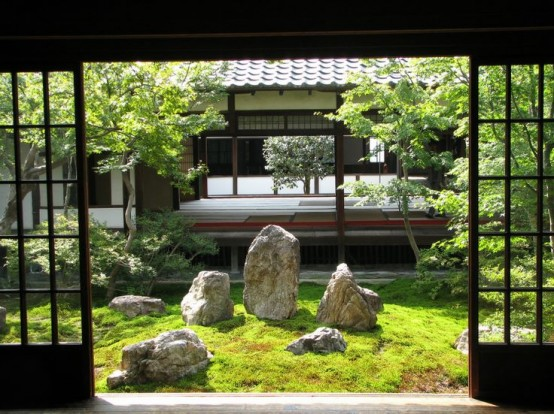 a classic Japanese garden with grass, large rocks and Japanese-style low trees