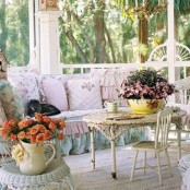 a shabby chic porch with elegant vintage furniture, cute floral pillows and potted greenery and flowers