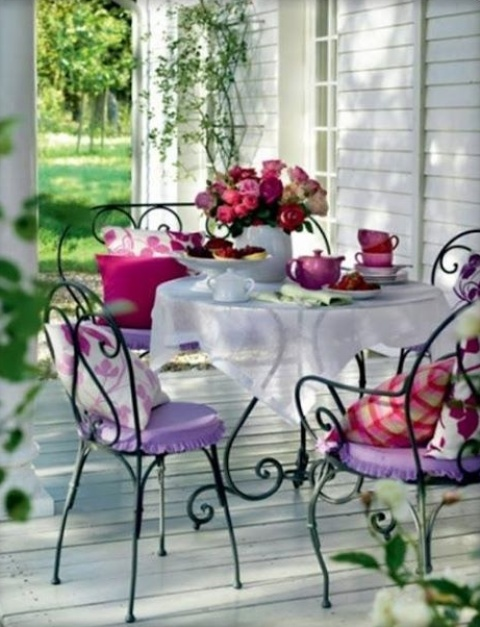 a cheerful summer porch with forged furniture, colorful cushions and pillows, tableware and greenery