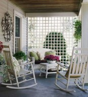 a simple vintage-inspired summer porch with white wicker furniture, bright pillows, potted greenery and blooms