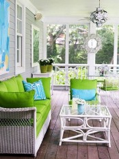 a bright and fresh summer porch with white wicker furniture, bright green and blue textiles and a white rattan coffee table