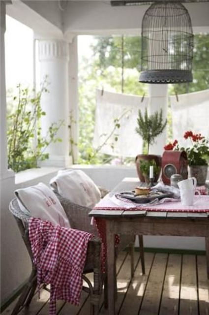 a cute summer porch with rattan and wood furniture, bright printed textiles, greenery and a suspended cage