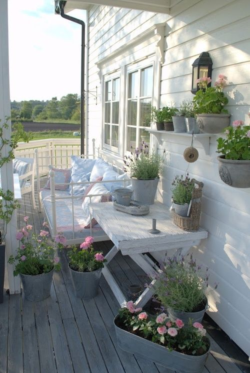 a welcoming summer porch with rustic and vintage furniture in white, potted blooms and greenery plus candle lanterns