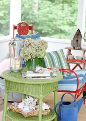 a colorful summer porch done in green and blue, with touches of red, candle lanterns and blooms