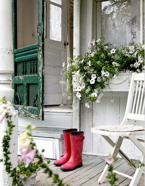 a white summer porch with shabby chic furniture and a door, rubber boots and potted flowers