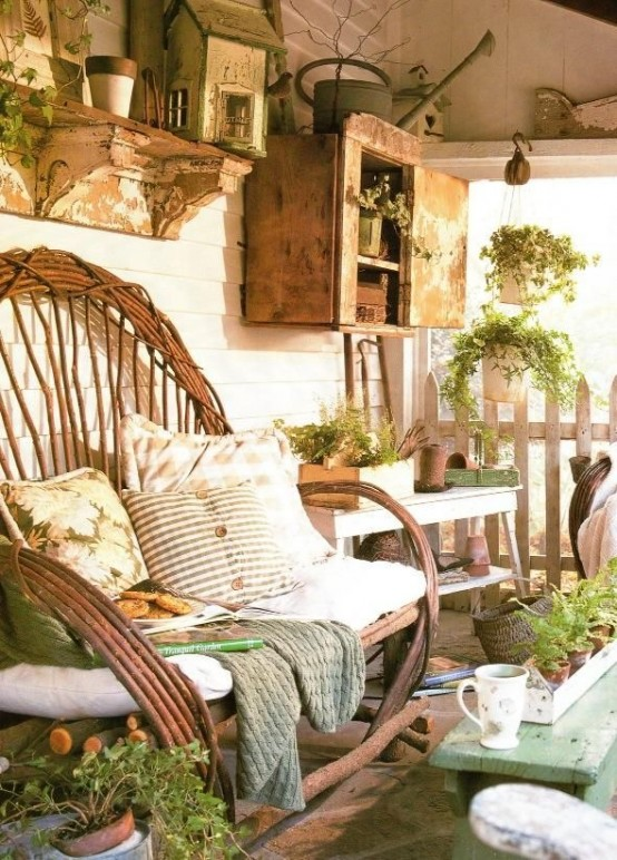 a rustic summer porch with wooden and rattan furniture, shabby chic cabinets and potted greenery