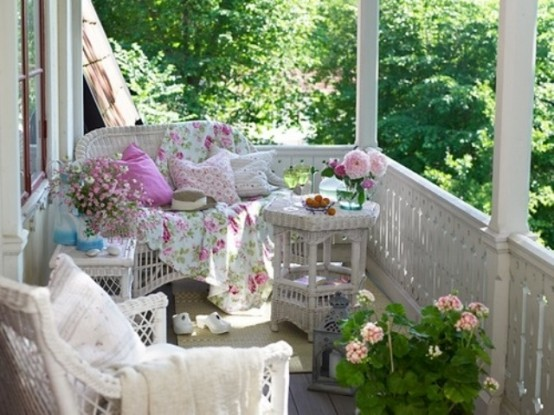 a vintage-inspired summer porch with white wicker furniture, bright and floral print textiles, potted blooms and candle lanterns