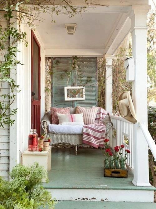 a small porch with a wicker loveseat, a bench, a crate and some colorful printed textiles