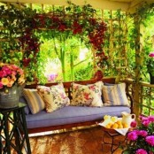 a colorufl summer porch with a ouch with bright pillows, a trellis with blooms and potted flowers and greenery