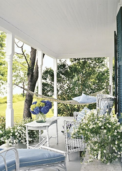 a pastel and neutral porch with wicker furniture, a hammock, potted blooms and greenery