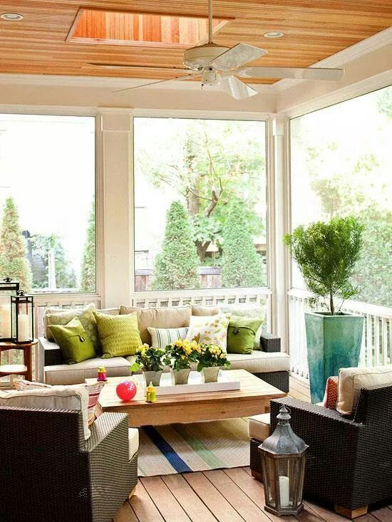 a modern summer porch with wicker furniture, bright pillows, candle lanterns and potted greenery and blooms