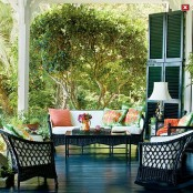 a lively summer porch done with dark wicker furniture, colorful printed pillows, a lamp and shutters