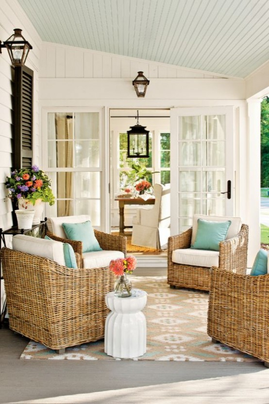 a rustic summer porch with wicker chairs, turquoise pillows and some potted blooms and greenery