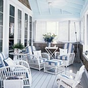 a coastal porch with white rattan furniture, striped navy and white upholstery, oars and shutters