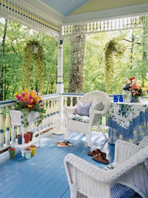 a bright blue summer porch with a blue floor, textiles, white furniture and potted blooms