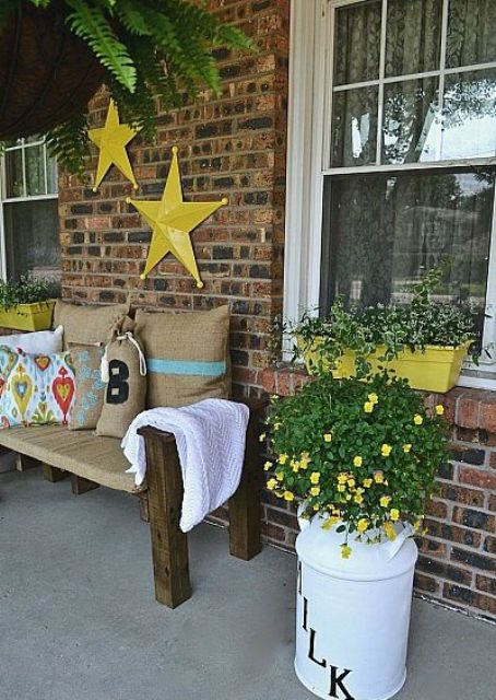 a rustic summer porch with a burlap covered bench, bright touches of yellow and potted flowers