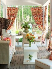 a cheerful summer porch with whiet wicker furniture, colorful pillows and curtains, a living and dining zone