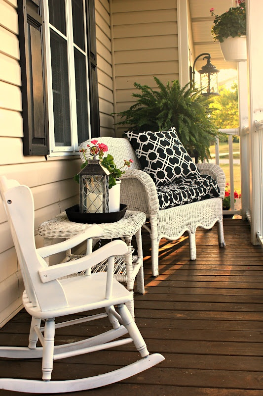 a small rustic porch with white wicker and wood furniture, candle lanterns and potted greenery