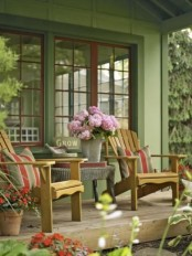 a welcoming rustic porch with wooden chairs and a wicker coffee table, potted blooms and a bucket with flowers