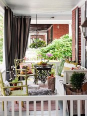 a colorful summer porch with yellow rattan chairs, a white bench, tree stump tables and bright textiles