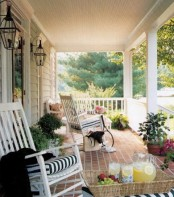 simple summer porch decor with white chairs with striped cushions, potted greenery and blooms, a basket for storage