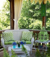 white wicker furniture, green printed textiles, grene signage and lanterns for a welcoming summer porch