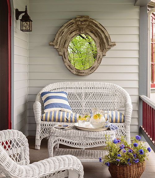 a summer porch with white wicker furniture, blooms in a basket, a shabby chic mirror and printed textiles