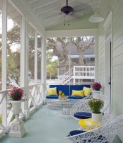 a colorful summer porch in bright yellow and blue, with catchy metal furniture and potted flowers