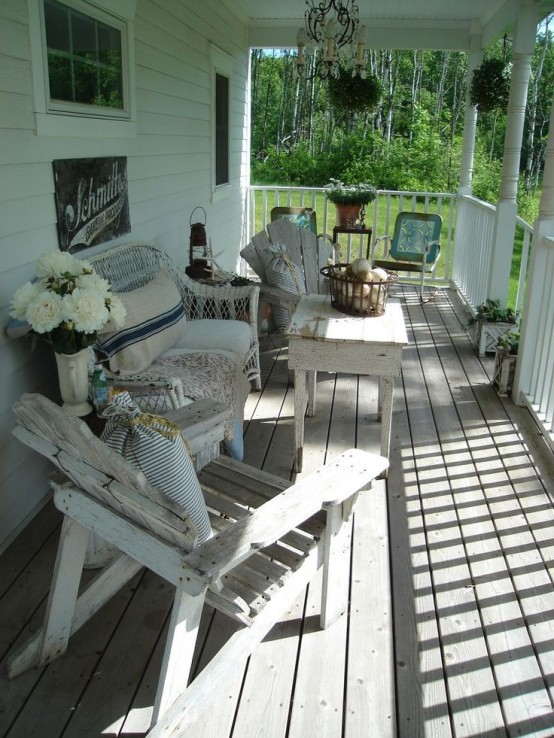 a neutral and relaxed summer porch with shabby chic and weathered wooden furniture, wicker pieces and some greenery and blooms