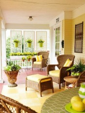 a bright summer porch with wicker furniture, sunny yellow textiles and accessories plus lots of potted flowers and greenery