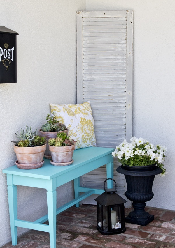 a beachy summer porch with a blue console, a whitewashed shutter, a candle lantern and potted succulents and blooms