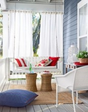 a bright summer porch with white wicker furniture, colorful pillows and white candle lanterns