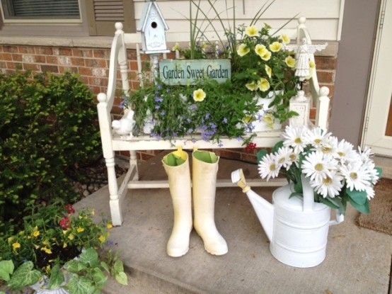 a small porch decorated with a vintage bench with potted blooms, a sign, a watering can with blooms and rubber boots