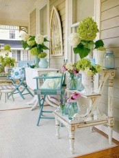 a shabby chic summer porch done with blue and neutral furniture and bright floral arrangements