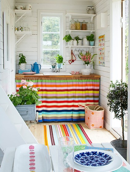 a bright kitchen with striped curtains, bold rugs, bright tableware and bold blooms and greenery