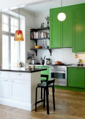 a chic kitchen in bold green, a white tile backsplash and a white ktichen island with black countertops