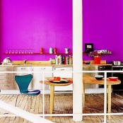 a vibrant kitchen with a hot pink wall, neutral cabinetry, wooden tables and a navy chair is a fantastic statement