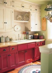 a bright kitchen with neutral and fuchsia cabinets, a neutral backsplash and some vintage decor