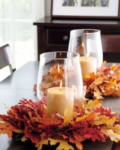 oversized glasses with pillar candles placed on large faux leaf wreaths form amazing bold centerpieces for a fall tablescape