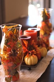 a clear vase with faux fall leaves and berries plus a stand with faux blooms, pumpkins and fall-colored candles