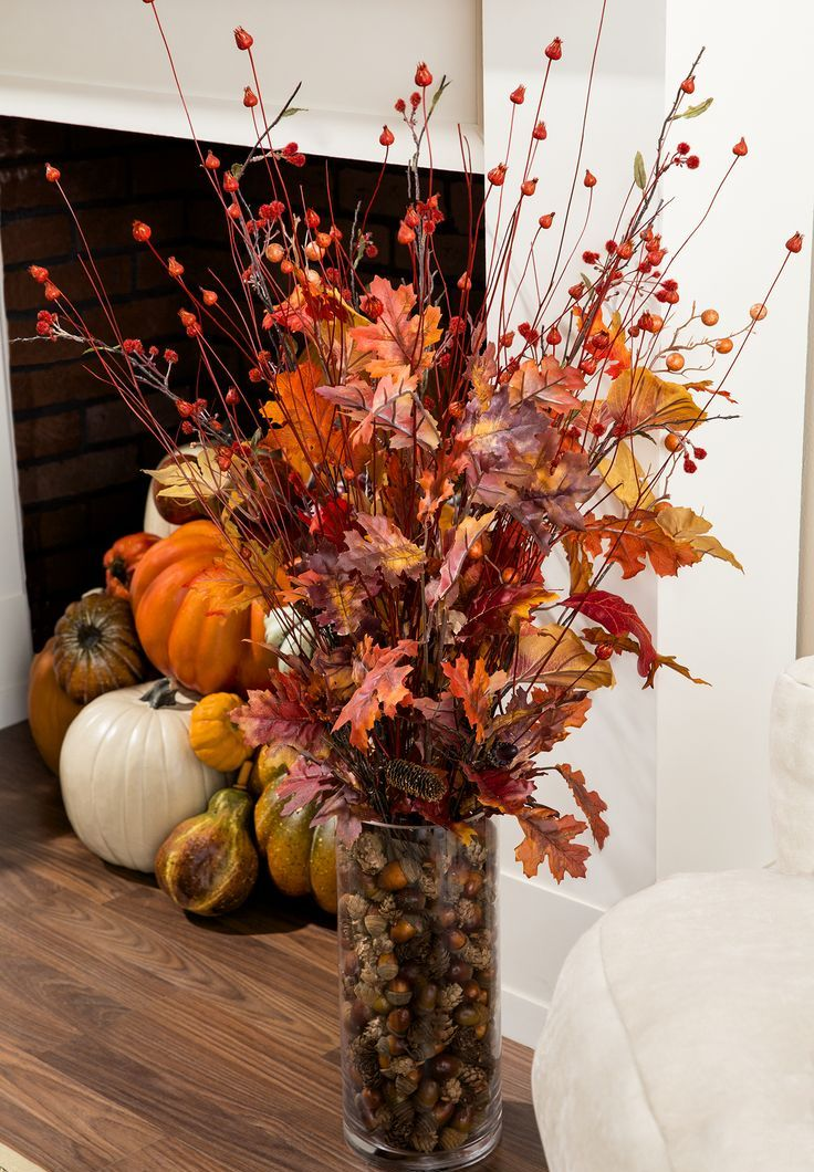 a clear vase with acorns and pinecones, fall leaves and berries and branches is a cool natural fall centerpiece