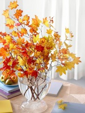 a modern fall centerpiece of a clear glass vase and lots of bold fall leaves is very chic