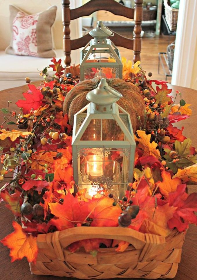 a basket centerpiece with fall leaves, berries, acorns, candle lanterns and a faux pumpkin is a cozy rustic centerpiece
