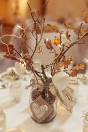 a jar with pinecones, branches with leaves, bells, lights and hearts as a creative fall decoration