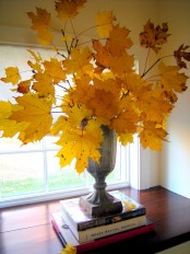 a refined vintage urn with lots of bright yellow fall leaves is a cool fall centerpiece or just decoration