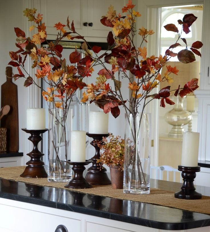 clear vases with dark fall leaves and candles in refined wooden candle holders are chic and stylish for a rustic tablescape